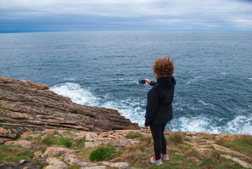 Mature redhead woman taking a picture with the cell phone, on her back, dressed to play sports in black. With the coast and the sea in the background, a cloudy spring afternoon