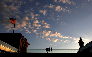 People are seen on the roof of the lower house of parliament Bundestag at the Reichstags building in Berlin