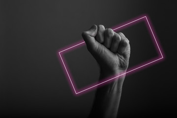 Raised clenched fist against a dark background with abstract neon light glow Fototapete