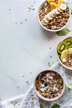 Healthy breakfast concept, cereal granola food with fruit in bowl organic muesli morning diet oat meal on white table, vegan background and detox snack for health nutrition vertical close up top view