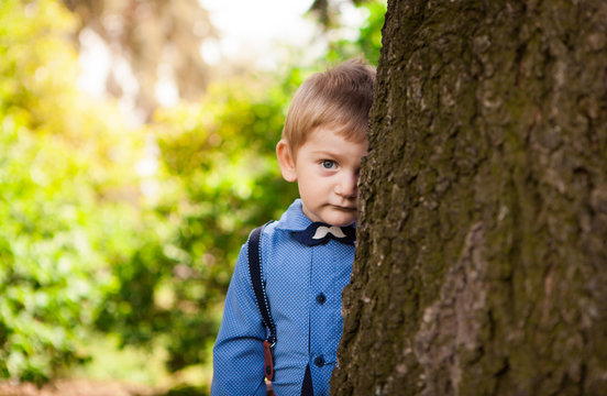 Cute little boy leaning against big tree and shy in summer, child portrait outdoors