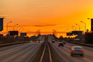 Symmetrical overpass extending beyond the horizon in the yellow orange light of the setting sun at the sunset. Nagaevskoe highway, Ufa, Bashkortostan, Russia - June 2015.