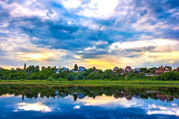 The quiet blue water with the reflection of the sky with massive low clouds, yellow rays of the sun above the green overgrown shore, private country houses. Kashkadan Lake, Ufa, Bashkortostan, Russia.
