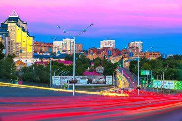 Bright red yellow trail lights of passing cars along the avenue in a modern city at sunset at dusk in summer evening against a pink blue sky. Sochi street, Ufa, Bashkortostan, Russia - June 2015.