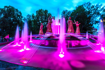Sculptures of beautiful girls in national dresses in a multi-colored highlight against the background of the night evening sky. Seven Girls Fountain, Ufa, Bashkortostan, Russia - June 2015.