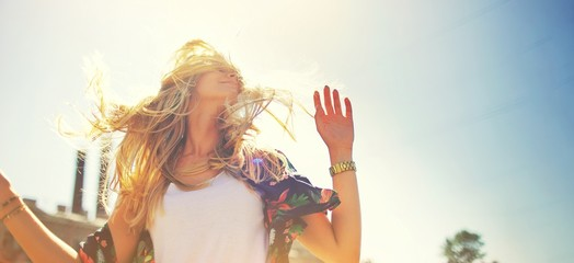 Attractive happy young woman in white t shirt flying hair enjoying her free time at sunset outdoor. Beauty blonde girl portrait at summer. Freedom lifestyle springtime concept. Sun glow on background. Fototapete