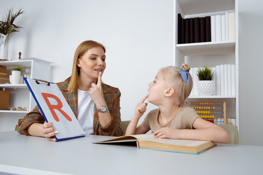 Cute girl with speech therapist in cabinet trainiing pronunciation