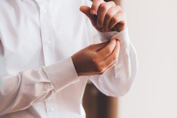 Man fixing cufflinks on his white shirt