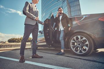 Handsome businessman in sunglasses is going out from car while his assistant is opening door for him.