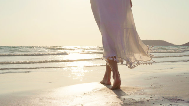 Young Asian woman walking on beach. Beautiful female happy relax walking on beach near sea when sunset in evening. Lifestyle women travel on beach concept.