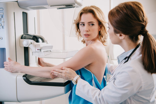 young radiologist preparing patient for mammography diagnostics on x-ray machine