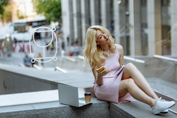 Happy young blonde female student in rose dress and white sneakers sit on the floor and listening music on the smartphone opposite building in city center. Laptop and cup coffee near.