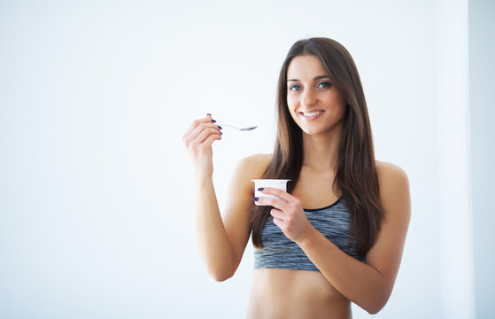 Diet. Happy young woman eating yogurt in kitchen