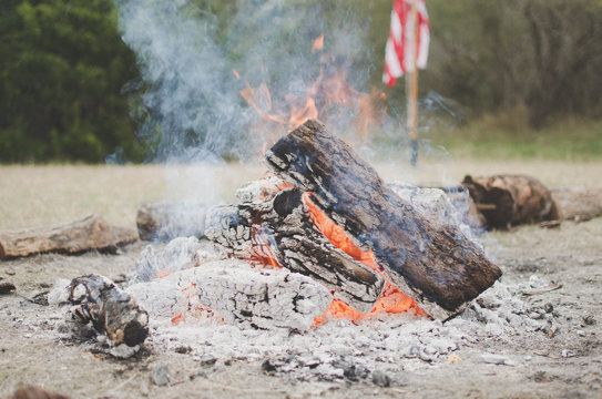 American flag behind campfire in the woods
