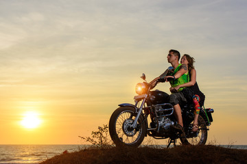 Romantic picture with a couple of beautiful stylish bikers at sunset. Handsome guy with tatoo and young sexy woman enjoy themselves in motorbike trip.