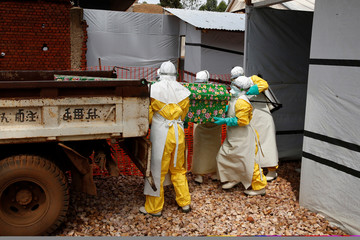 Health workers dressed in Ebola protective suits place a coffin containing the body of an Ebola patient to a truck at an Ebola treatment centre in Butembo