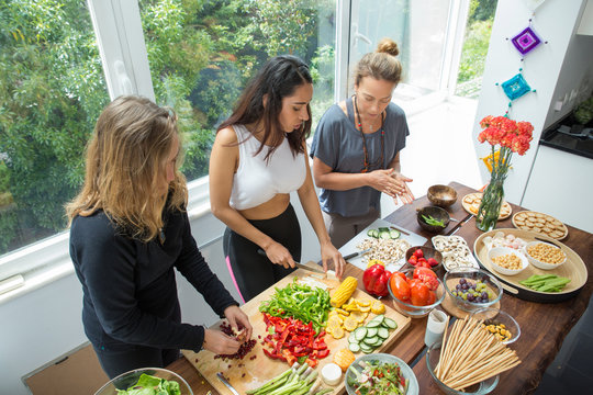Serious ladies cooking and cutting vegetables at kitchen table. Women standing at table with fresh vegetables and window with green view in background. Healthy cooking and summer concept.