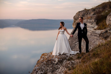 Sensual wedding couple standing holding hands together on the background of mountains and sea