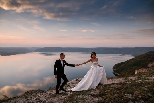 Sensual wedding couple groom and bride in a long white dress standing on the edge of the mountains overlooking the lake holding hands together