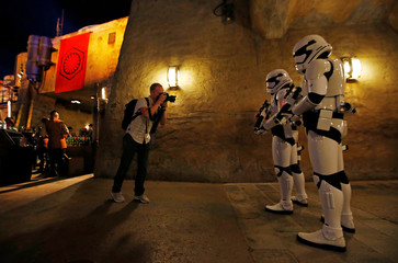"A man takes photographs of people dressed as stormtroopers at ""Star Wars: Galaxy's Edge"" at Disneyland Park in Anaheim"