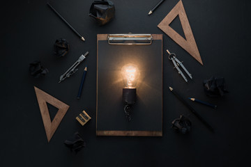 Light bulb in black on black flat lay with architect tools, rulers and pencils. Idea for engineering, building or construction with copy space.