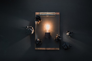 Light bulb shining in flat lay with crumpled paper balls and a clipboard. The idea for engineering, building or construction concept with copy space.