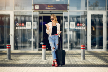 Girl in a airport. Blonde with a documents. Lady in a black t-shirt
