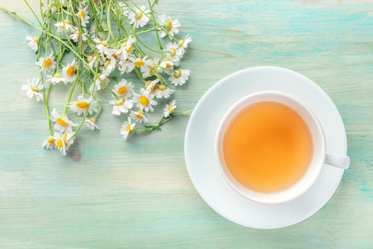 A cup of chamomile tea, shot from the top on a teal blue background with a bouquet of flowers and a place for text