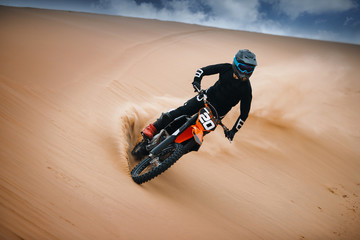 Motorcyclist on a cross-country motorcycle go fast at the desert