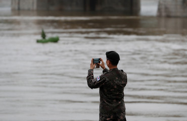 Military official from the South Korean Embassy takes photos at the Danube river bank in Budapest