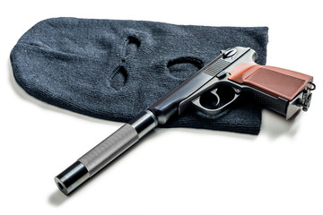 black balaclava and a pistol with a silencer close up on a white table - fototapety na wymiar