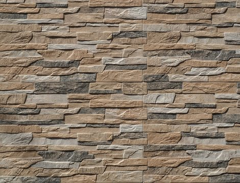 Stone wall cladding made of stripes artificial rocks. The colors are black,brown and gray Background, close up.