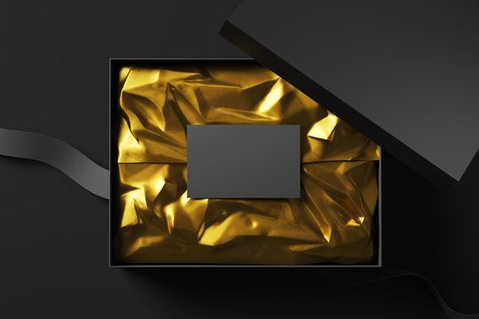 Realistic black open cardboard box with golden wrapping paper and business card and fabric tape. Top view. Mock up. 3d rendering