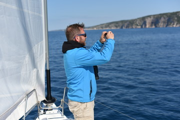 Man sailing with sails out on a sunny day and taking photos with his smartphone