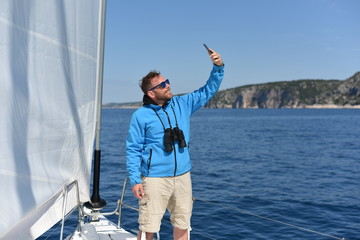 Man sailing with sails out on a sunny day and making selfie