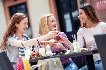 Female friends eat pizza in cafe
