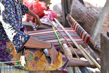 Indonesian woman in a shop producing Songket Lombok in the village Sukarara which is located in the south of the Lombok island, Indonesia Wall mural