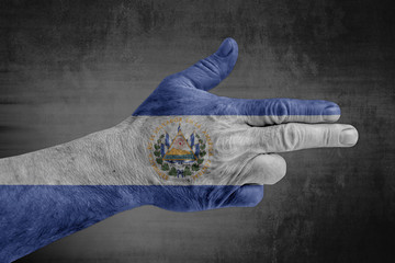 El Salvador flag painted on male hand like a gun