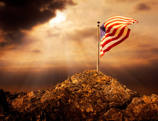 Conceptual image of waving American flag at tall pole over cloudy sunset sky