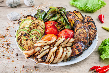 Close up view on grilled vegetables on white plate served on white wooden table. tomato, pepper, eggplant, zucchini and onion cooked over charcoal. Copy space, picture for barbecue. Healthy food