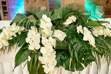 Lush floral arrangement of orchids and monstera leaves on wedding table. Wedding presidium in restaurant, copy space. Banquet table for newlyweds. Luxury wedding decor