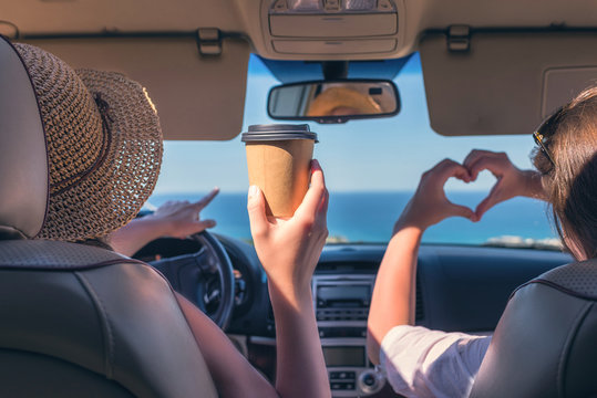 Two girls traveling by car on the Italy. One of them  holds her hands in the form of heart
