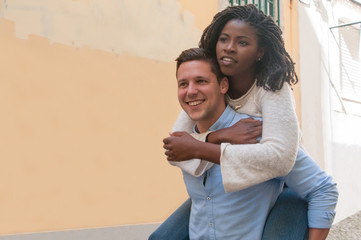 Guy carrying black girlfriend on back in city. Happy interracial couple in street. Romance and happiness concept. Front view.