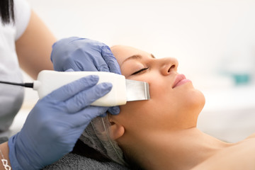 Beautiful woman receiving skin cleansing procedure in cosmetologically clinic