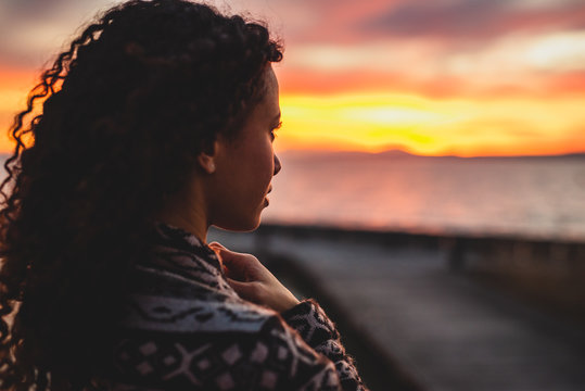 Thoughtful evening mood with a young Afro American woman standing on the promenade by the lake and looking towards the water and the setting sun. Burning sky