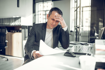 Businessman having too many complications working on report