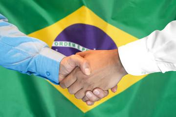 Business handshake on Brazil flag background. Men shaking hands and Brazil flag on background. Support concept