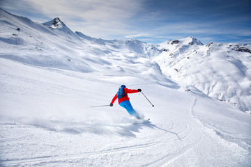 Fototapete - Young attractive skier skiing in famous ski resort in Alps, Livigno, Italy, Europe