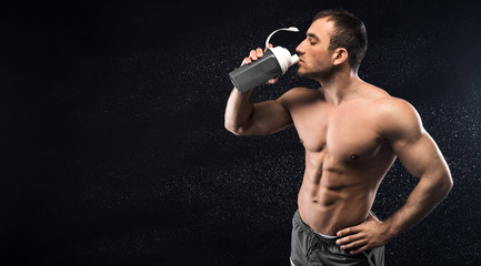 Young sporty man drinking energy cocktail in studio