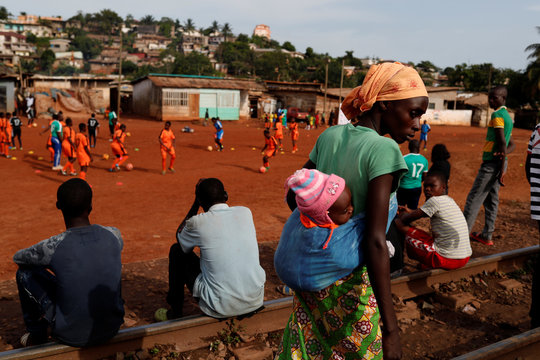 A woman carrying her child walks past people sitting on train tracks as they watch a training session of the U17, a team of first wave of girls being trained by professional coaches of the Rails Foot Academy (RFA) at the RFA field in Yaounde